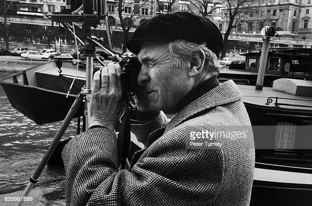 Photographer Robert Doisneau shoots photos along the Seine next to barges and boats