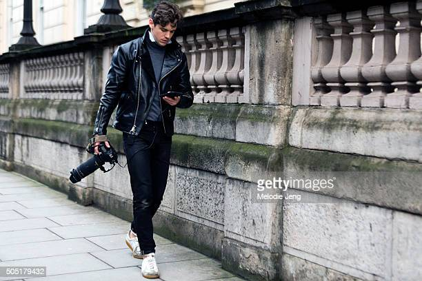 Photographer Robert Spangle checks his phone carries a Nikon camera and wears a black Vanson leather Left Field jacket black Left Field jeans a Boggi...
