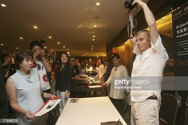 Photographer Robert Whitaker holds his camera above his head at the autograph signign session at his photographic exhibition during the events to...