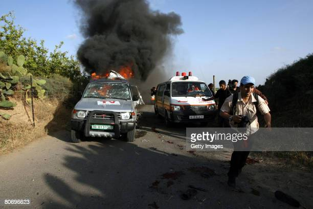 A photographer runs away from the burning car of Reuters cameraman Fadel Shaana after it was hit by an Israeli missile on April 16 2008 in central...