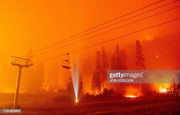 Photographer shines a flashlight towards a chair lift as flames surround Sierra-at-Tahoe Resort, a skiing area, during the Caldor fire in Twin...