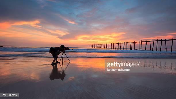 photographer shooting a bridge into the sea at sunset. - 三脚 ストックフォトと画像