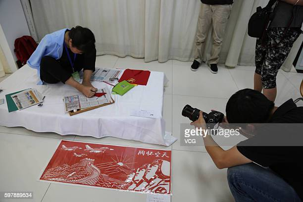 A photographer shoots armless girl Xia Hong tracing on red paper with her feet during a handcraft competition on August 29 2016 in Beijing China 232...