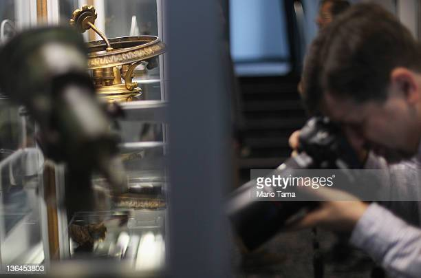 A photographer shoots artifacts recovered from the RMS Titanic wreck site at a press preview of a Titanic artifact auction at the Intrepid Sea Air...