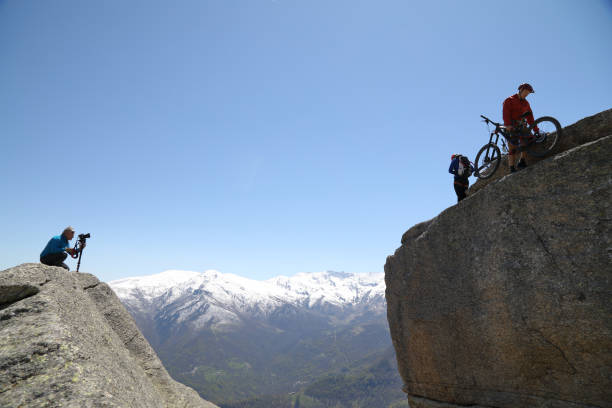 Photographer shoots mountain bikers as they prepare to rappel (abseils) from overhanging cliff