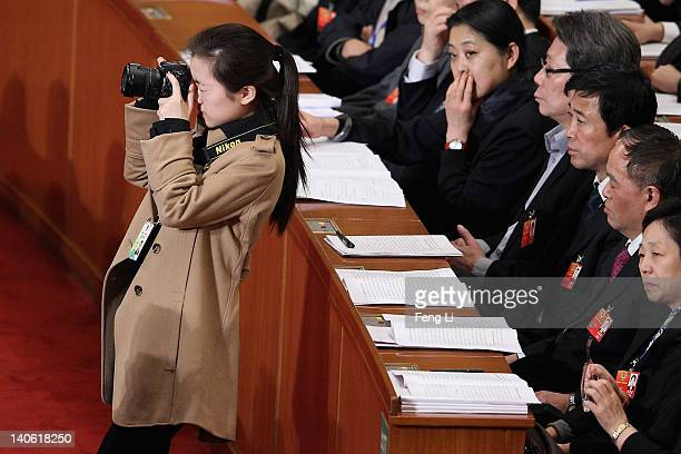 Photographer shoots pictures during the opening ceremony of the Chinese People's Political Consultative Conference at the Great Hall of the People on...