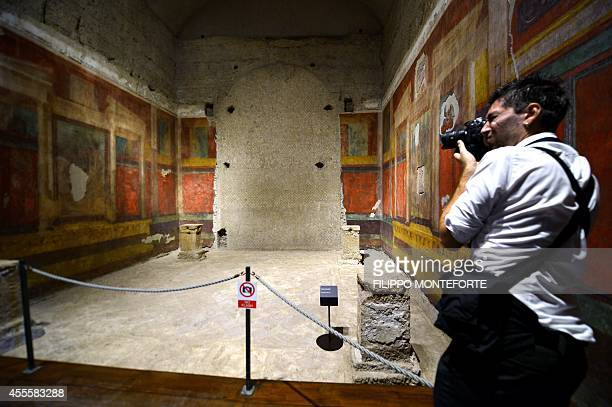 A photographer shoots pictures inside a room at the House of Augustus on the Palatine hill in Rome on September 17 2014 The house of Emperor Augustus...