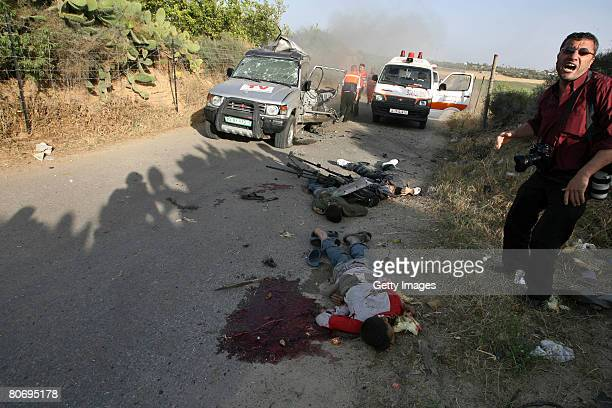 A photographer shouts as he stands next to bodies including the body of Reuters cameraman Fadel Shaana as he lies on the road after his car was hit...