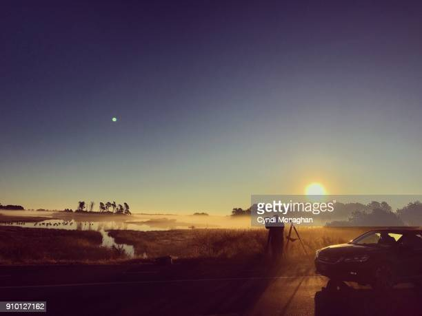 Photographer Silhouetted in Mist and Sunrise