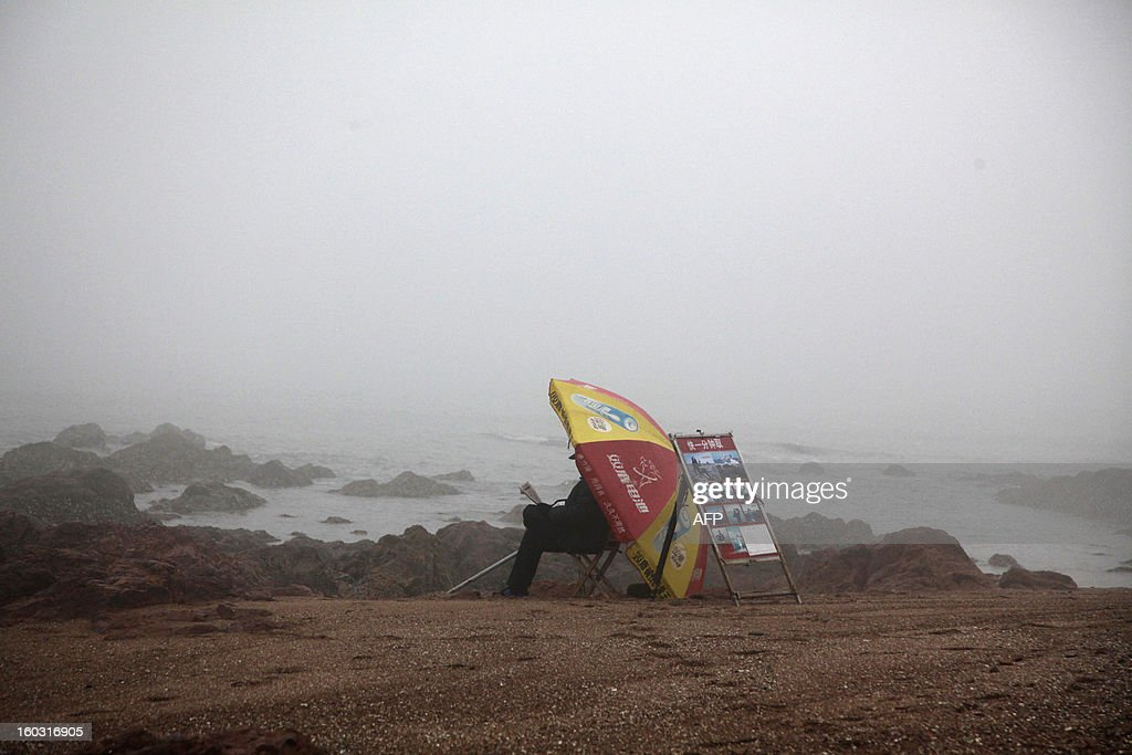 A photographer sit in the smog-covered beach in Qingdao, east China's Shandong province on January 29, 2013. Residents across northern China battled through choking pollution on January 29, as air quality levels rose above index limits in Beijing amid warnings that the smog may not clear until January 31. CHINA