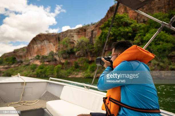 photographer sitting boat takes a picture river - photojournalist stock pictures, royalty-free photos & images