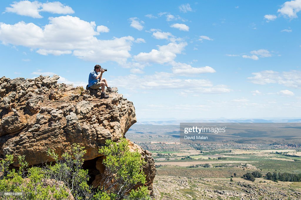 Photographer sitting on hill taking a photograph. : Stock Photo