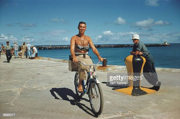 Photographer Slim Aarons riding a bike along the quayside with cameras slung round his neck during the filming of 'Mister Roberts' in Hawaii