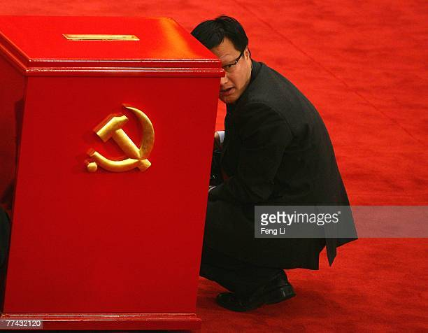 Photographer squats beside the beallot box during the Chinese Communist Party Congress at the Great Hall of the People on October 21, 2007 in...