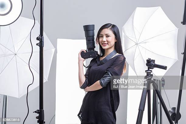 Photographer standing in studio with camera