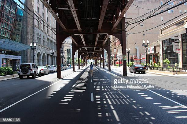 Photographer Standing In The Middle Of The Street With L Train Overhead