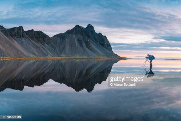 photographer standing on a mirroring layer of water, iceland - 三脚 ストックフォトと画像