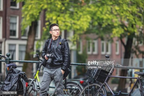 Photographer standing on bridge over Amsterdam canal, Netherlands