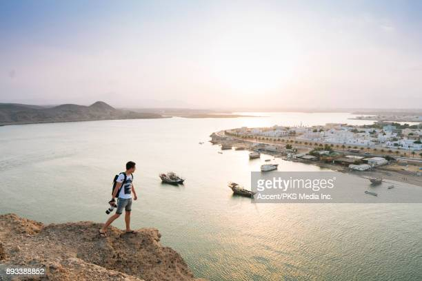 Photographer standing on cliff overlooking Middle Eastern sea port