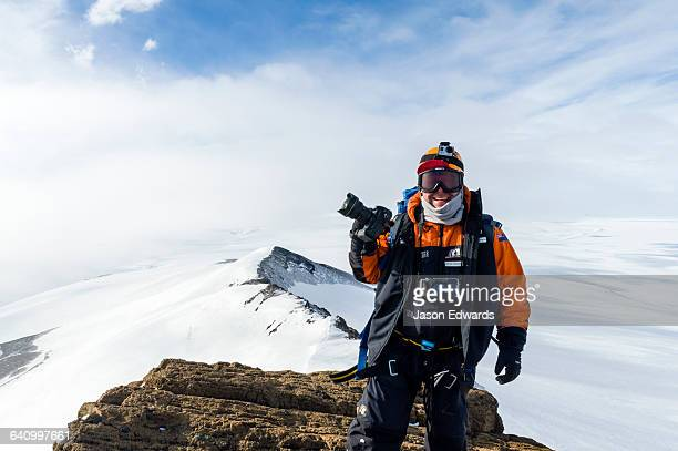 A photographer standing with his camera on a mountaintop in Antarctica.