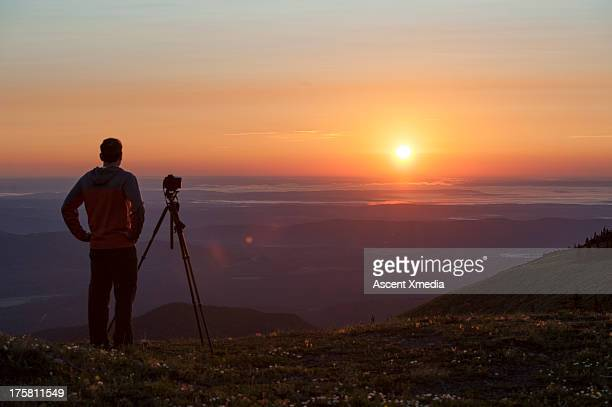 Photographer stands on hill above sunrise, waiting