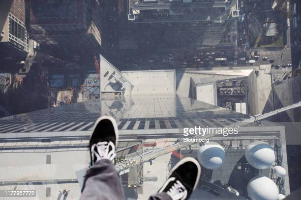 A photographer stands on the glass floor of the Edge observation deck at 30 Hudson Yards during a media preview event in New York US on Thursday Oct...