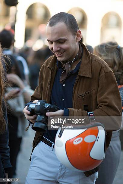 Photographer Stephane Buttice wears brown suede jacket, blue knit button up shirt and neckerchief after Dior at Cour Carree Du Louvre during Paris...