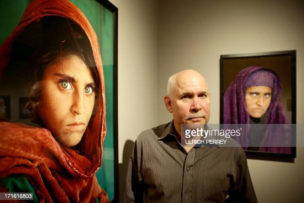US photographer Steve McCurry poses next to his photos of the 'Afghan Girl' named Sharbat Gula at the opening of the 'Overwhelmed by Life' exhibition...