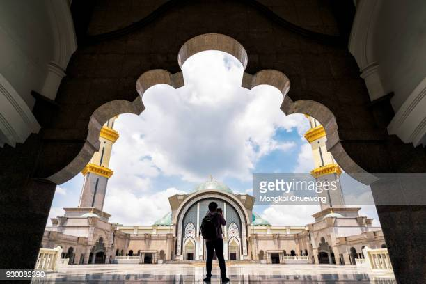 photographer take a photo in masjid wilayah persekutuan or mosque wilayah at kuala lumpur malaysia - place of worship stock pictures, royalty-free photos & images