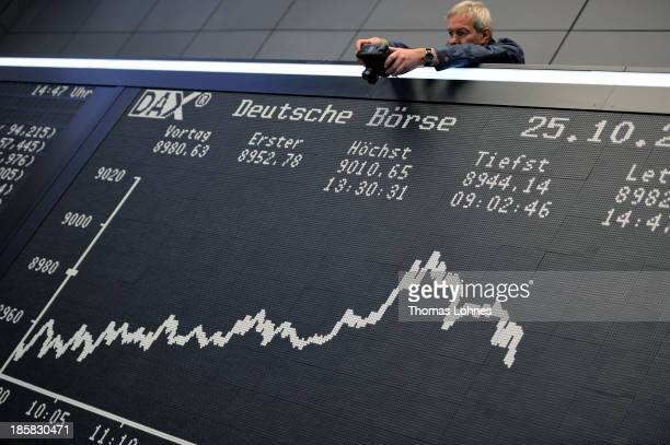 A photographer takes a photo of today's performance board of the DAX stock market index not long after the DAX broke the 9000 level at the Frankfurt...