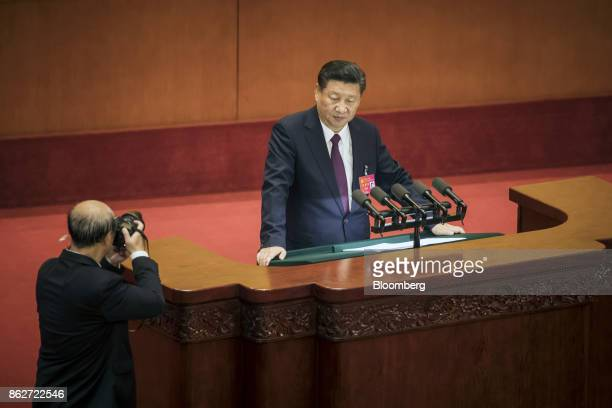 Photographer takes a photograph of Xi Jinping, China's president, as he pauses while giving a speech during the opening of the 19th National Congress...