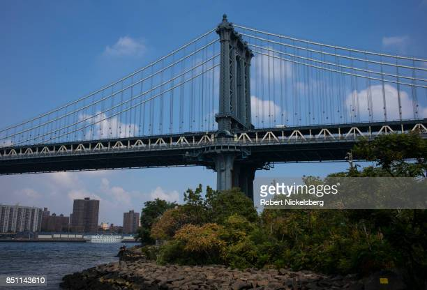 A photographer takes a picture along the East River near the Manhattan Bridge September 16 2017 in Brooklyn New York The suspension bridge was opened...