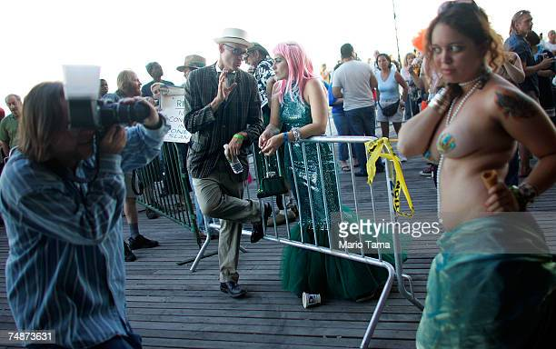 A photographer takes a picture as revelers gather following the annual Coney Island Mermaid Parade June 23 2007 in the Brooklyn borough of New York...