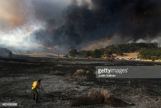 A photographer takes a picture as the Rocky Fire burns on a ridge above a ranch on July 30 2015 in Lower Lake California Over 600 firefighters are...
