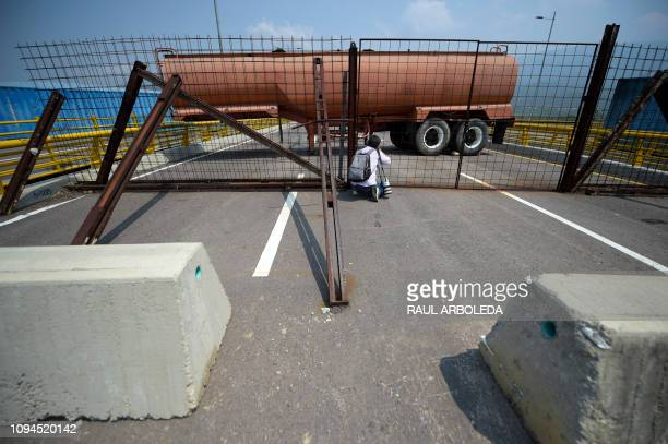 TOPSHOT A photographer takes a picture as Venezuelan military forces block with containers the Tienditas Bridge which links Tachira Venezuela and...