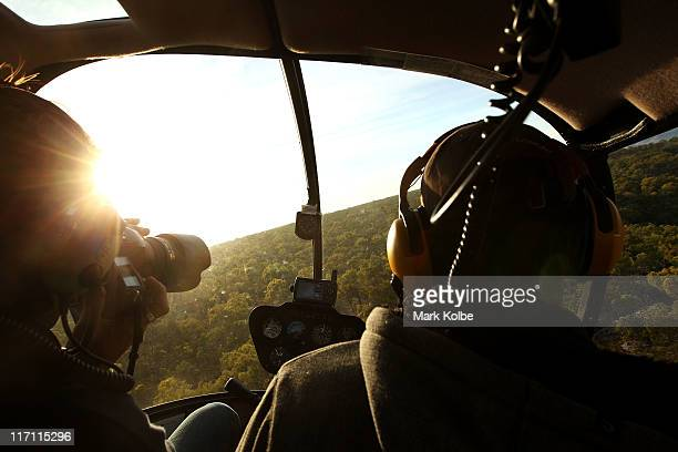 A photographer takes a picture during a helicopter flight to visit the Giant Horse Aboriginal rock art galleries in the Quinkan Country on June 19...