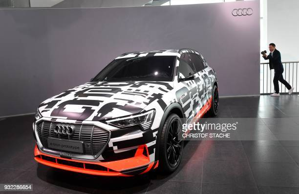 A photographer takes a picture of an Audi etron prototype car prior to annual press conference at the headquarters in Ingolstadt on March 15 2018 /...