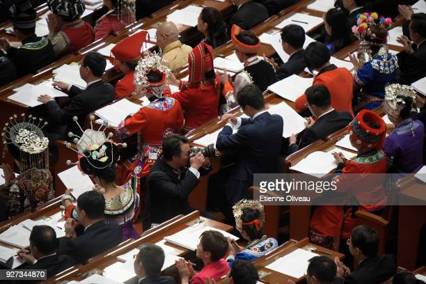 Photographer takes a picture of an ethnic minority delagate during the opening session of the 13th National People's Congress at The Great Hall of...