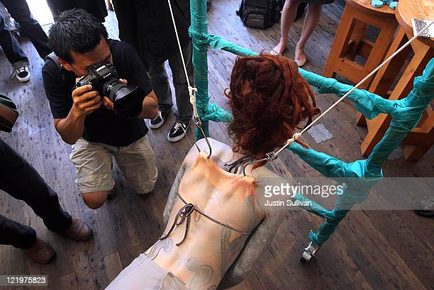A photographer takes a picture of suspension artist and LUSH Cosmetics employee Alice Newstead as she hangs from a scaffold by shark hooks that she...