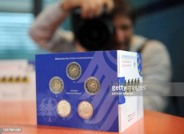 A photographer takes a picture of the 2 euro commemorative coin '25 Jahre Deutsche Einheit' in the Chancellery in Berlin Germany 29 January 2015...