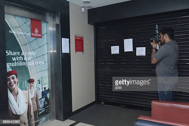 A photographer takes a picture of the closed Emirates airline office with notices confirming that flight EK521 travelling from Thiruvananthapuram to...