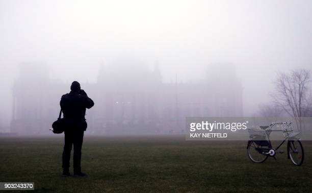A photographer takes a picture of the fog covered Reichstag building that houses the lower house of Parliament 'Bundestag' in Berlin on January 10...
