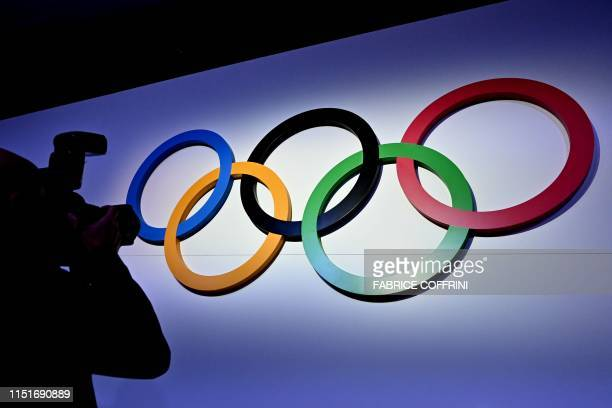 A photographer takes a picture of the Olympic Rings at the opening of the 134th session of the International Olympic Committee held to decide which...