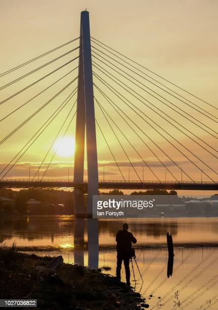 A photographer takes a pictures as the sun rises behind the new Northern Spire bridge spanning the River Wear on the day that it opens for a...