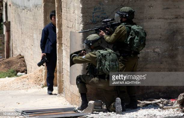 Photographer takes cover as Israeli forces stand behind a wall during clashes with Palestinian demonstrators following a weekly demonstration against...