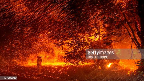 Photographer takes photos amidst a shower of embers as wind and flames rip through the area during the Kincade fire near Geyserville, California on...