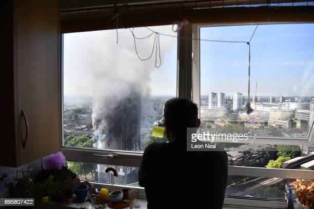 A photographer takes photos as smoke continues to rise from the building after a huge fire engulfed the 24 storey residential Grenfell Tower block in...