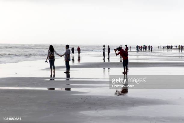 Cox´s Bazar Bangladesh October 14 2018 A photographer takes photos of a couple on the beach The beach of Cox's Bazar wIth 120 km long sandy beach it...