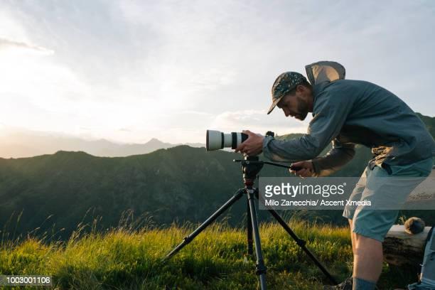 photographer takes pics at sunrise, on mountain top - 三脚 ストックフォトと画像