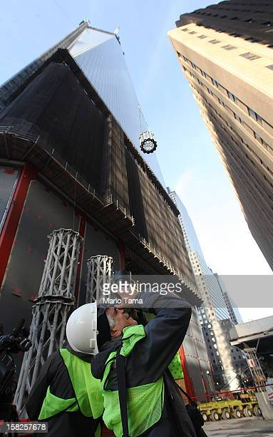 A photographer takes pictures as the first piece of the spire is hoisted atop One World Trade Center on December 12 2012 in New York City The first...